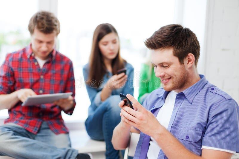 Student, der in der Schule Smartphone untersucht lizenzfreies stockfoto