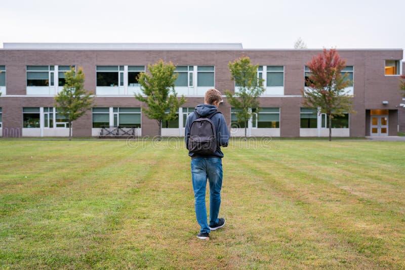 Student, der durch einen Fußballplatz geht lizenzfreie stockfotos