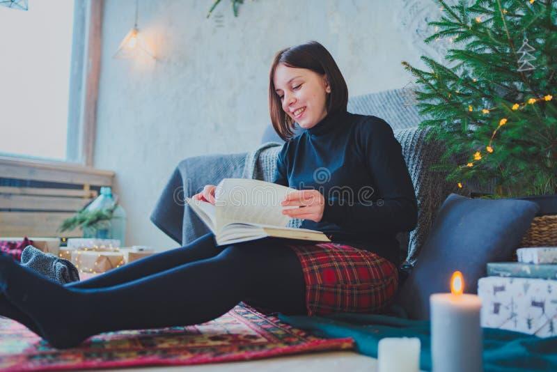 Student, der ein Buch in einem gem?tlichen Raum liest Frau, die ein Buch h?lt stockfotos