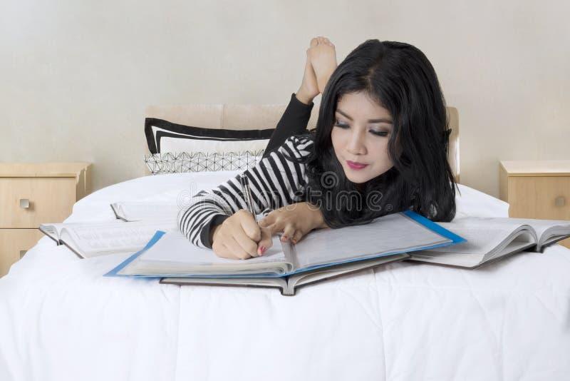 Student, der eine Anmerkung auf das Bett schreibt lizenzfreie stockfotografie