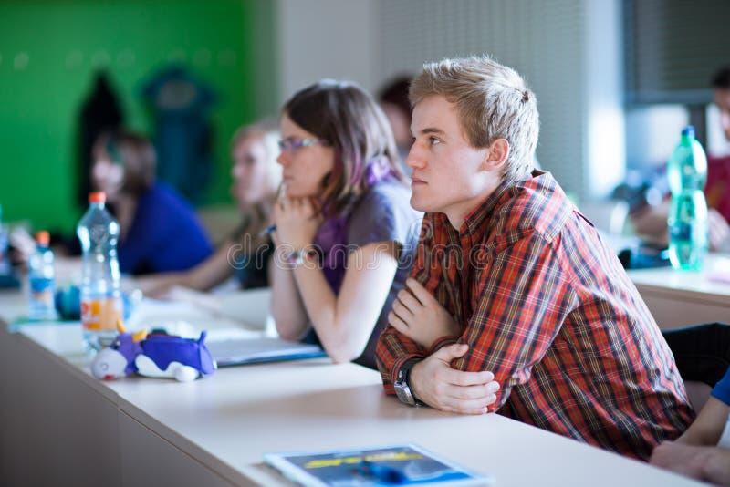 Student, der in einem Klassenzimmer sitzt lizenzfreie stockfotografie