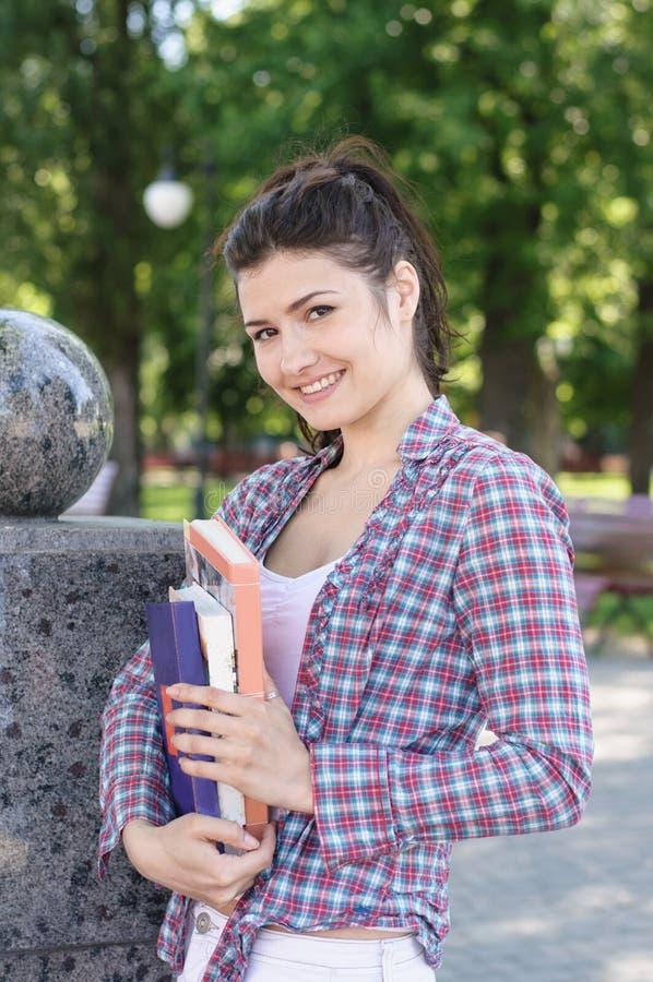 Student, der in einem Park, Bücher und das Lächeln halten steht stockbilder