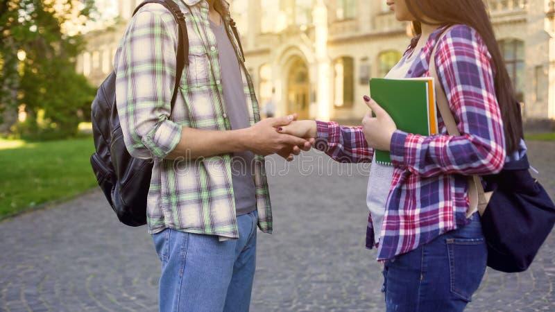 Student, der Freundinhand, spontane Datierung nahe College, Beziehungen hält lizenzfreie stockbilder