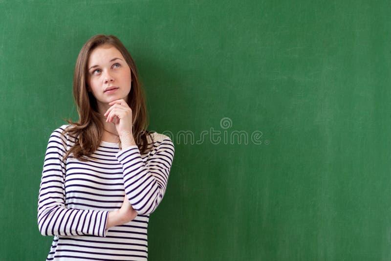 Student, der am grünen Tafelhintergrund denkt und sich lehnt Nachdenkliches Mädchen, das oben schaut Kaukasisches Studentinporträ stockfoto