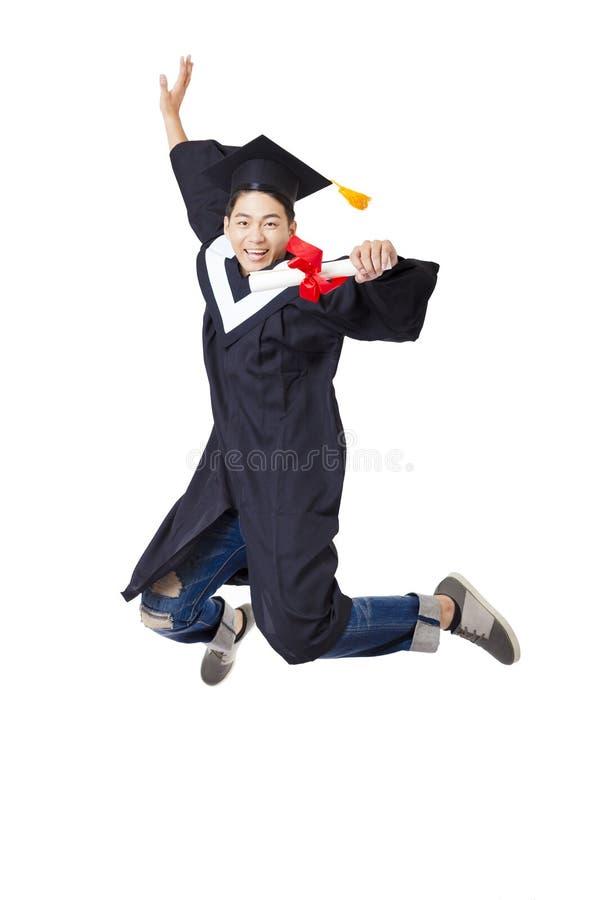 Student in der graduierten Robe, die gegen weißen Hintergrund springt stockfotografie