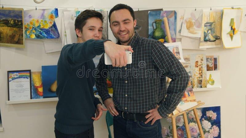 Student, der Hände mit seinem Kunstlehrer rüttelt und selfie am Telefon nimmt lizenzfreie stockbilder