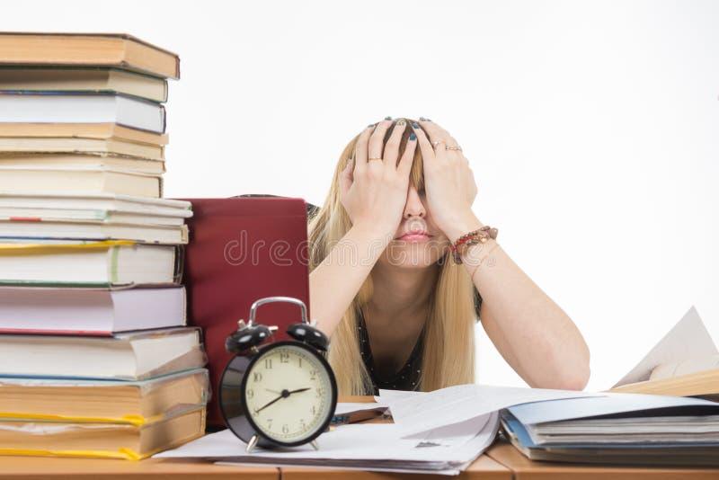 Student, der ihre Augen mit ihren Händen bedeckt, um eine Pause von ihren Studien zu machen lizenzfreie stockfotografie