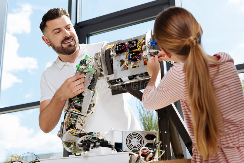 Student, der im Begriff ist, Drähte in Teil des Roboters zu verstopfen lizenzfreies stockfoto