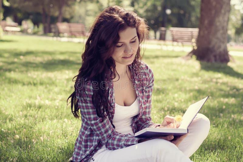 Student, der im Park auf dem Gras sitzt und ein Buch liest stockfotografie