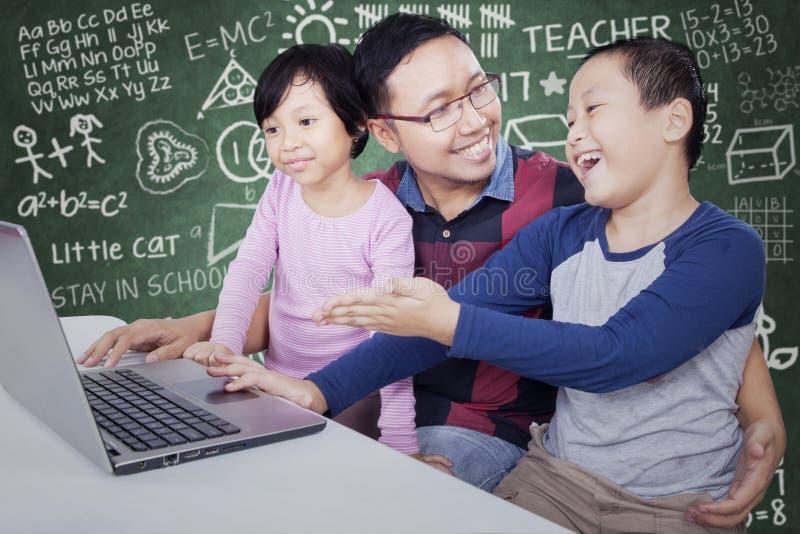 Student, der Laptop auf seinem Freund und Lehrer zeigt lizenzfreies stockfoto