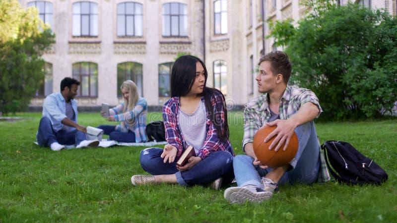 Student, der mit schönem asiatischem Mädchen auf Collegecampus sich verständigt und flirtet stockfoto