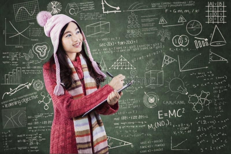 Student in der Strickjacke schreibt auf lipboard an der Klasse lizenzfreies stockbild
