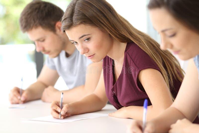 Student, der versucht, während einer Prüfung zu kopieren stockbild