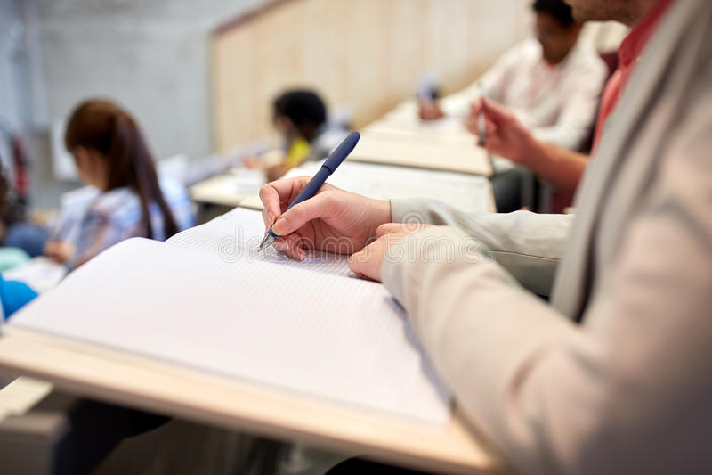 Student, der zum Notizbuch an der Prüfung oder am Vortrag schreibt stockbild