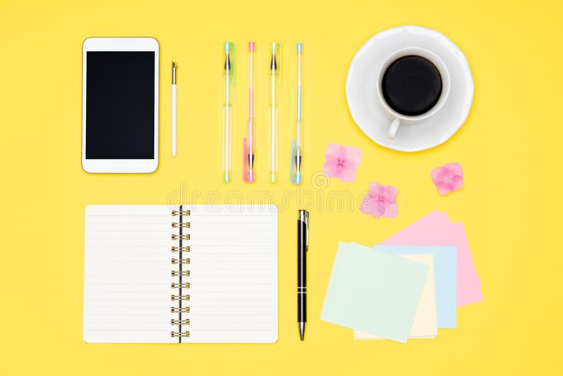 Top view of working space table with morning coffee, smartphone and stationery, office supplies on pastel yellow colored backgroun. Student desk flat lay. Top stock photo