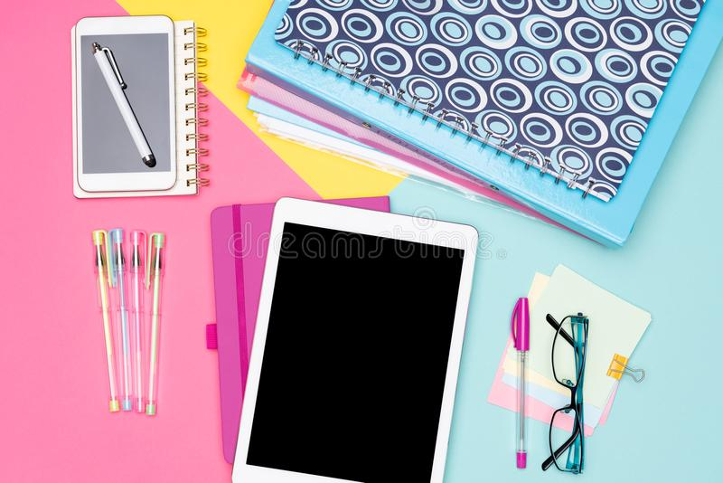 Student Desk Working Space Flat Lay. Top view photo of workspace with mock up tablet, folders and smartphone on pastel background. royalty free stock images