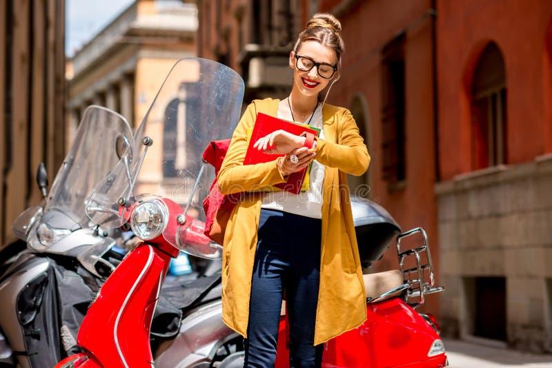 Student dichtbij rode autoped in de stad royalty-vrije stock afbeeldingen