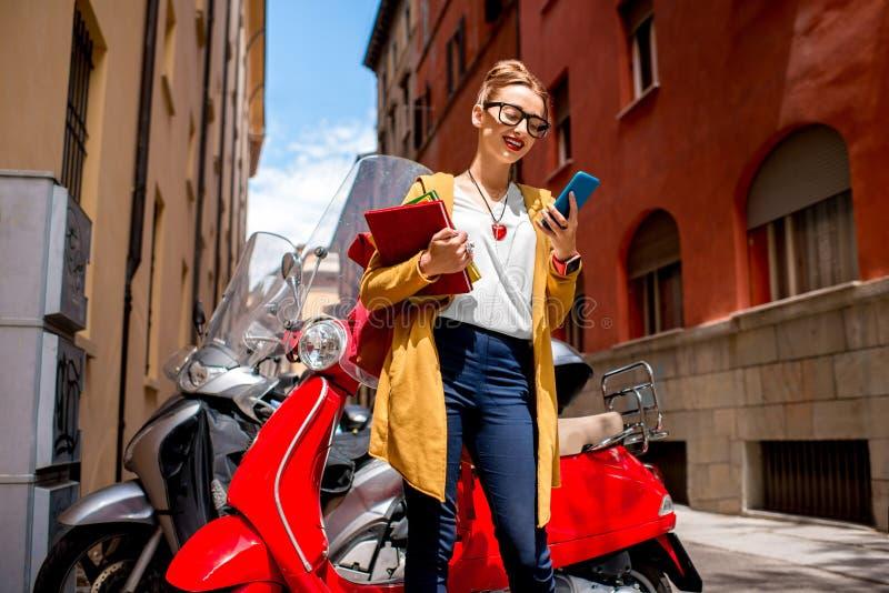 Student dichtbij rode autoped in de stad stock foto's