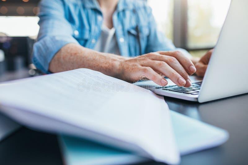 Student die aan laptop bij bibliotheek werken stock foto's