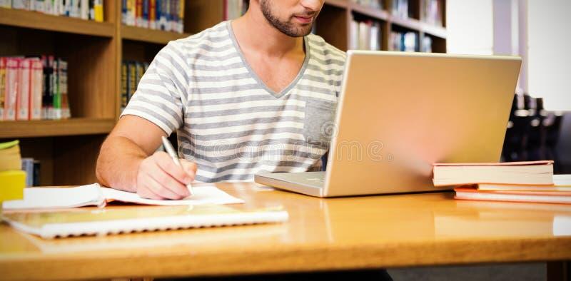 Student die in bibliotheek met laptop bestuderen stock afbeeldingen