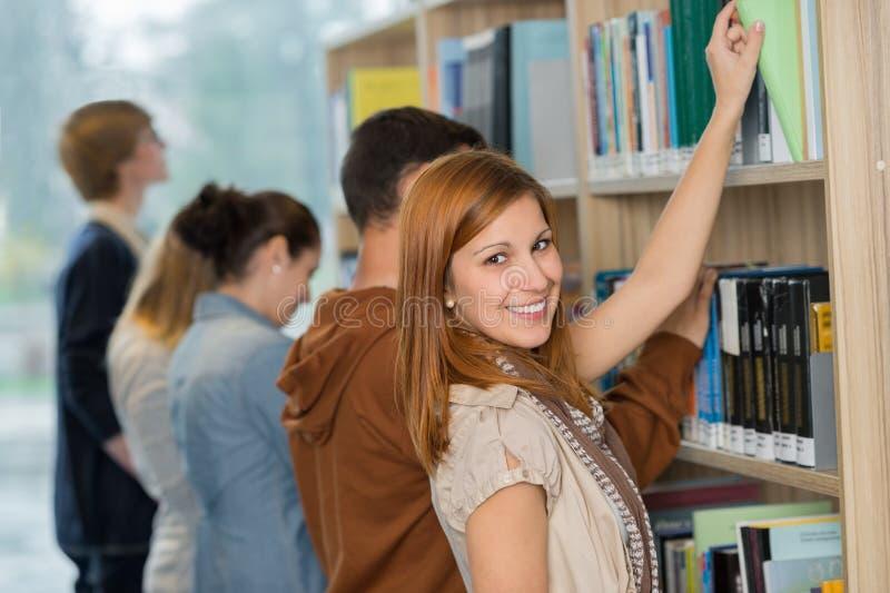 Student die boek kiezen van boekenrek in bibliotheek stock foto