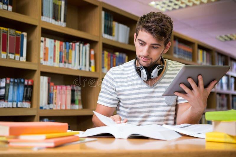 Student die in de bibliotheek met tablet bestuderen royalty-vrije stock foto's