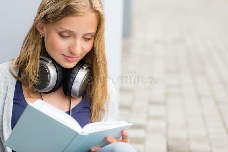 Student die een boek buiten universiteit leest stock afbeelding
