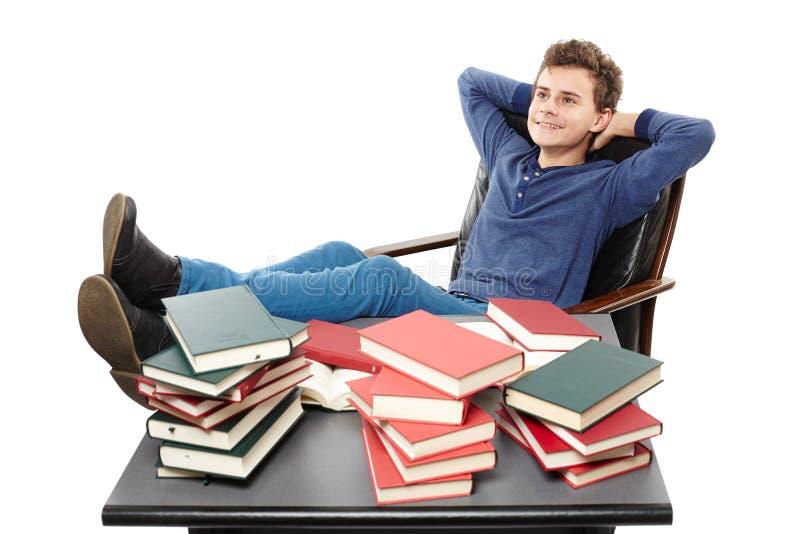 Student die een rust met de benen op het bureau hebben, die amo dagdromen royalty-vrije stock foto