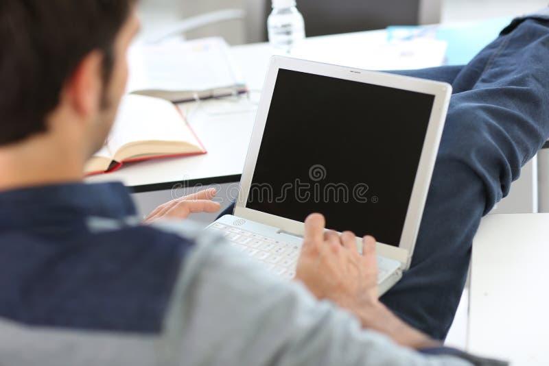 Student die gebruikend laptop ontspannen stock foto