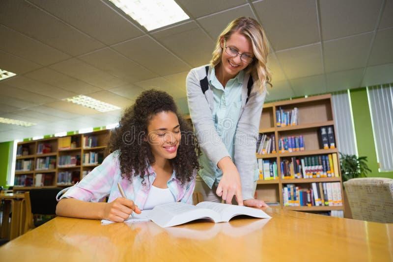 Student die hulp van privé-leraar in bibliotheek krijgen royalty-vrije stock foto