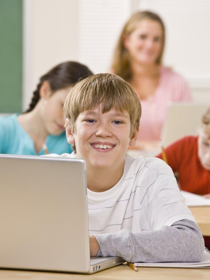 Student die laptop in klaslokaal met behulp van royalty-vrije stock foto's