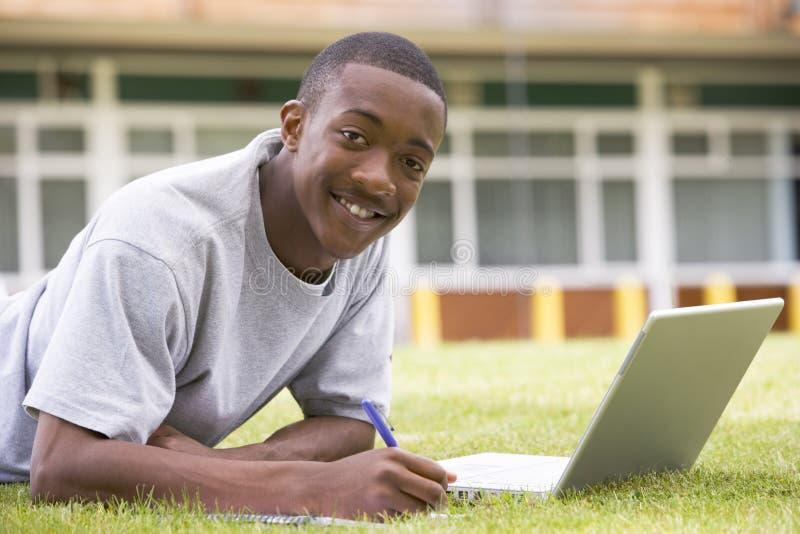 Student die laptop op campusgazon met behulp van stock foto's
