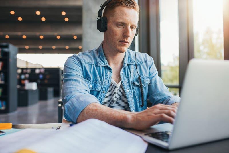 Student die laptop voor universitaire taak met behulp van royalty-vrije stock foto's