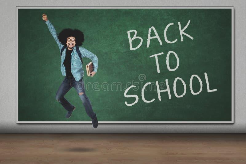 Student die met terug naar schooltekst springen royalty-vrije stock afbeelding