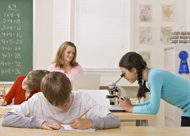 Student die microscoop in klaslokaal onderzoekt stock afbeelding