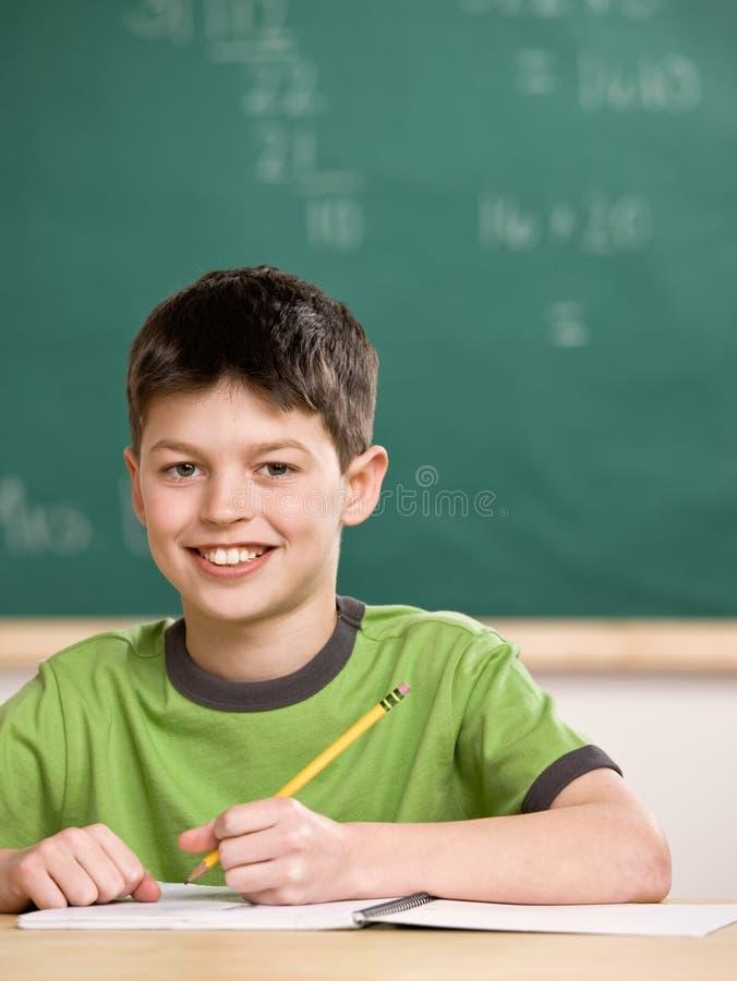 Student die in notitieboekje in schoolklaslokaal schrijft stock foto