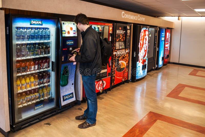 Student die voor de dranken van de automaat betalen royalty-vrije stock afbeeldingen