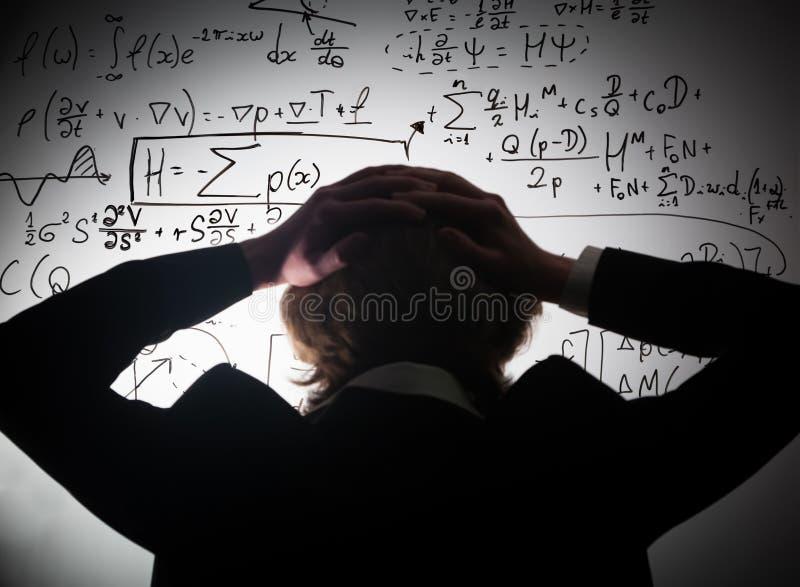 Student die zijn hoofd houden bekijkend complexe wiskundeformules op whiteboard Op te lossen probleem stock foto