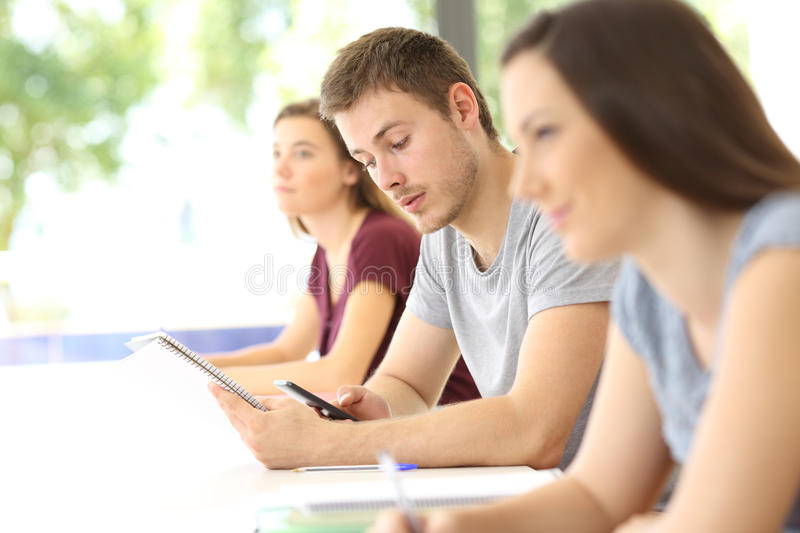 Student distracted with a phone during a class. Student distracted with a mobile phone during a class in a classroom royalty free stock photography