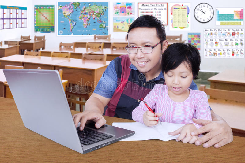Student doing school assignment with her teacher stock images
