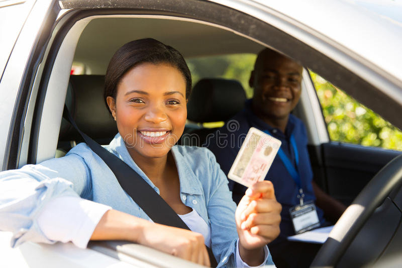 Student driver passes. African student driver passes driving test and holding her driver's license royalty free stock photography