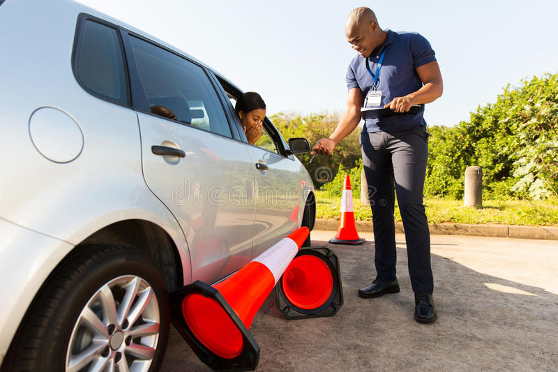 Student driving test. Student driver making mistake during driving test, running over traffic cones stock image