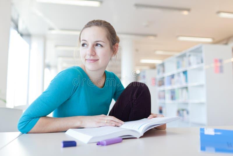 Student in een bibliotheek stock afbeelding