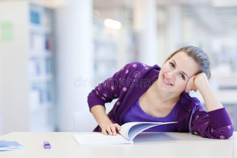 student in een bibliotheek stock foto