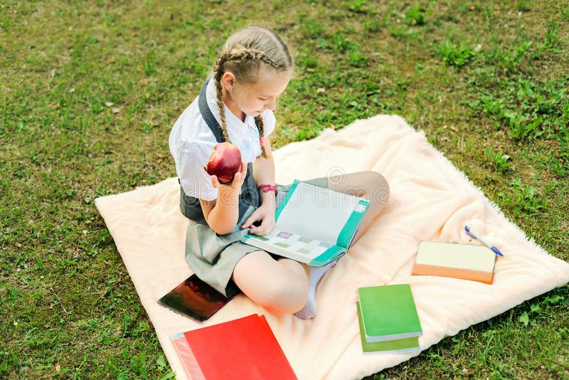 Student in eenvormig etend een rode appel schoolmeisjezitting op een deken in een park met boeken royalty-vrije stock fotografie