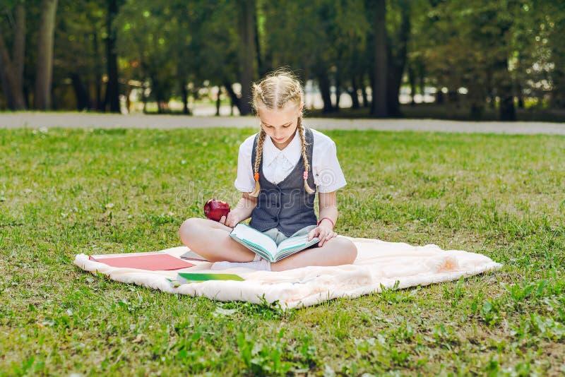Student in eenvormig etend een rode appel voor lunch schoolmeisjezitting op een deken in een park met boeken royalty-vrije stock foto's