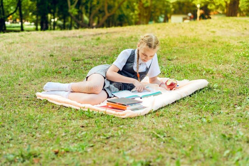 Student in eenvormig met vlechten die een rode appel voor lunch eten het schoolmeisje ligt op een deken in een park stock foto's