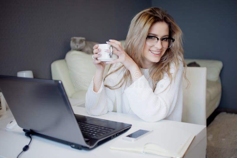 Student eller freelancer som hemma arbetar med bärbara datorn Den charmiga unga kvinnan sitter framme av bildskärm med koppen kaf royaltyfri bild