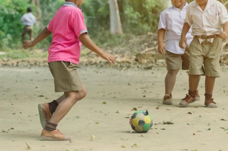 Student enjoy to play the old football with his friends on the ground. In school royalty free stock photos