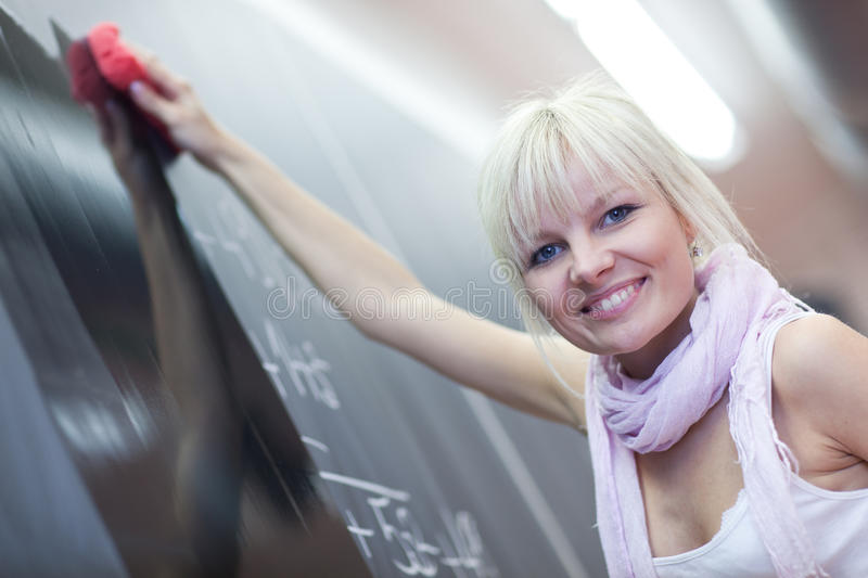 Student erasing the chalkboard. Pretty young college student erasing the chalkboard/blackboard during a math class stock image